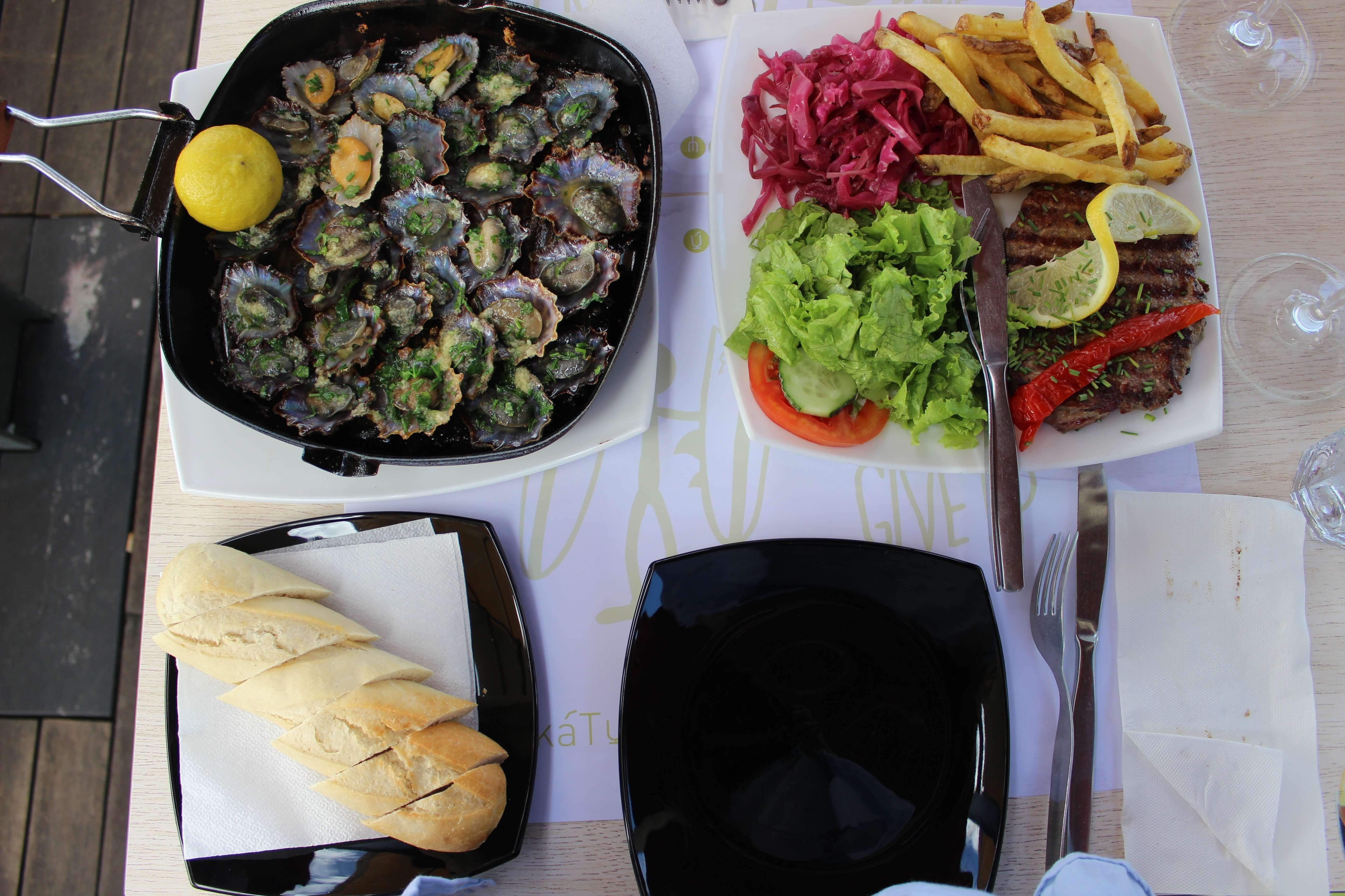 limpets, bread, and steak with dressings