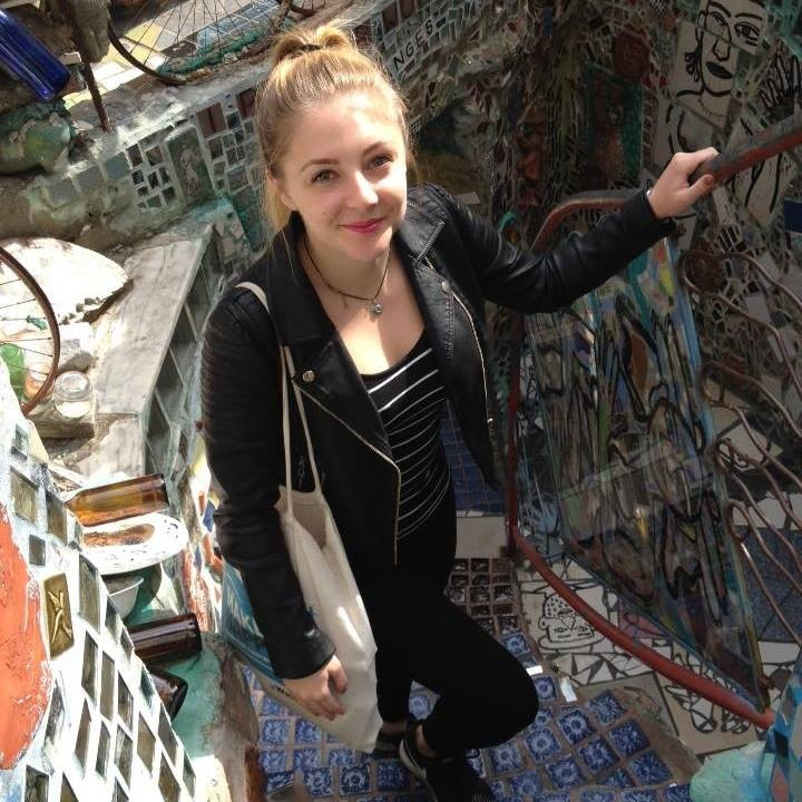 Wow Holy climbing the stairs near a wall mural on her travels