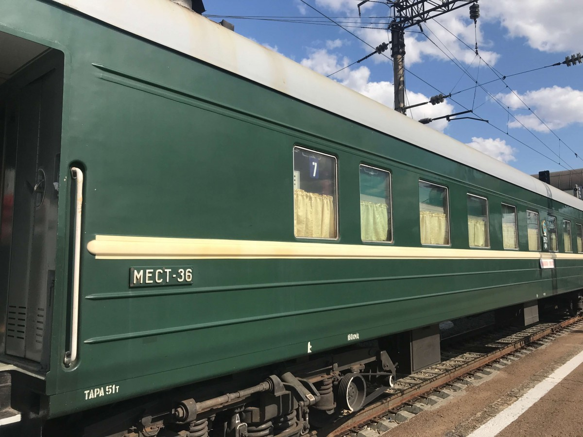 A green train carriage on the Trans-Mongolian railroad.