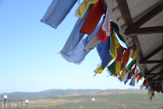 Colorful red, white, blue and yellow Buddhist prayer flags hang blowing in the wind over the Mongolian steppe.