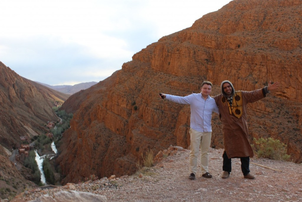 Dylan and our guide, Hicham, standing over the Dades Gorge smiling for the camera.