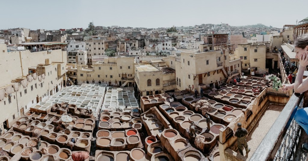 Giant cement vats with colorful liquid dyes lay out in a tannery in Morocco, stretched and crammed in between crowded streets which show behind them.