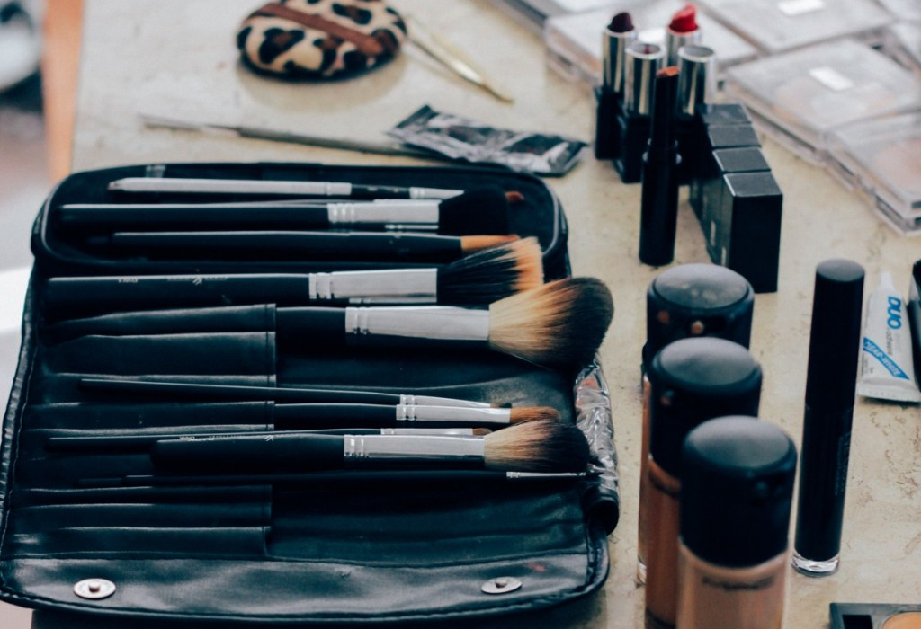 Photo of a makeup bag with brushes, lipstick, and nude foundations lined up on a tan countertop.