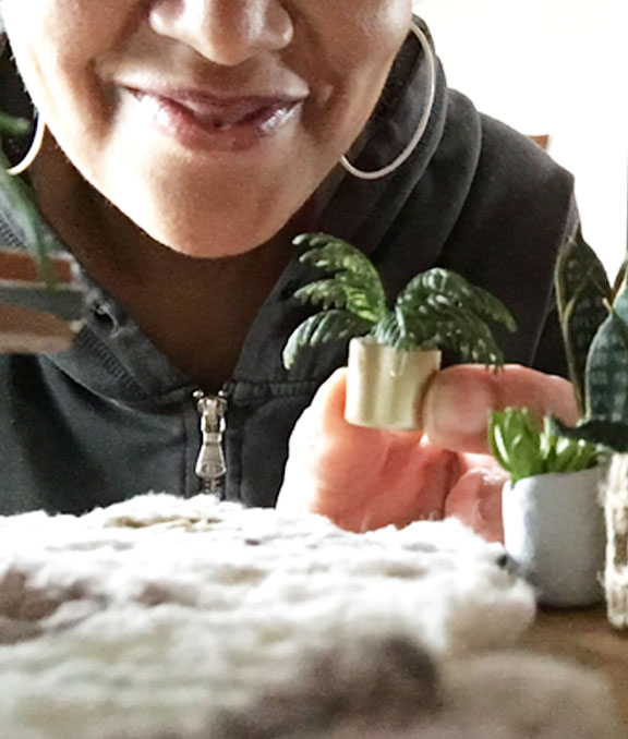 author placing miniature plant in diorama