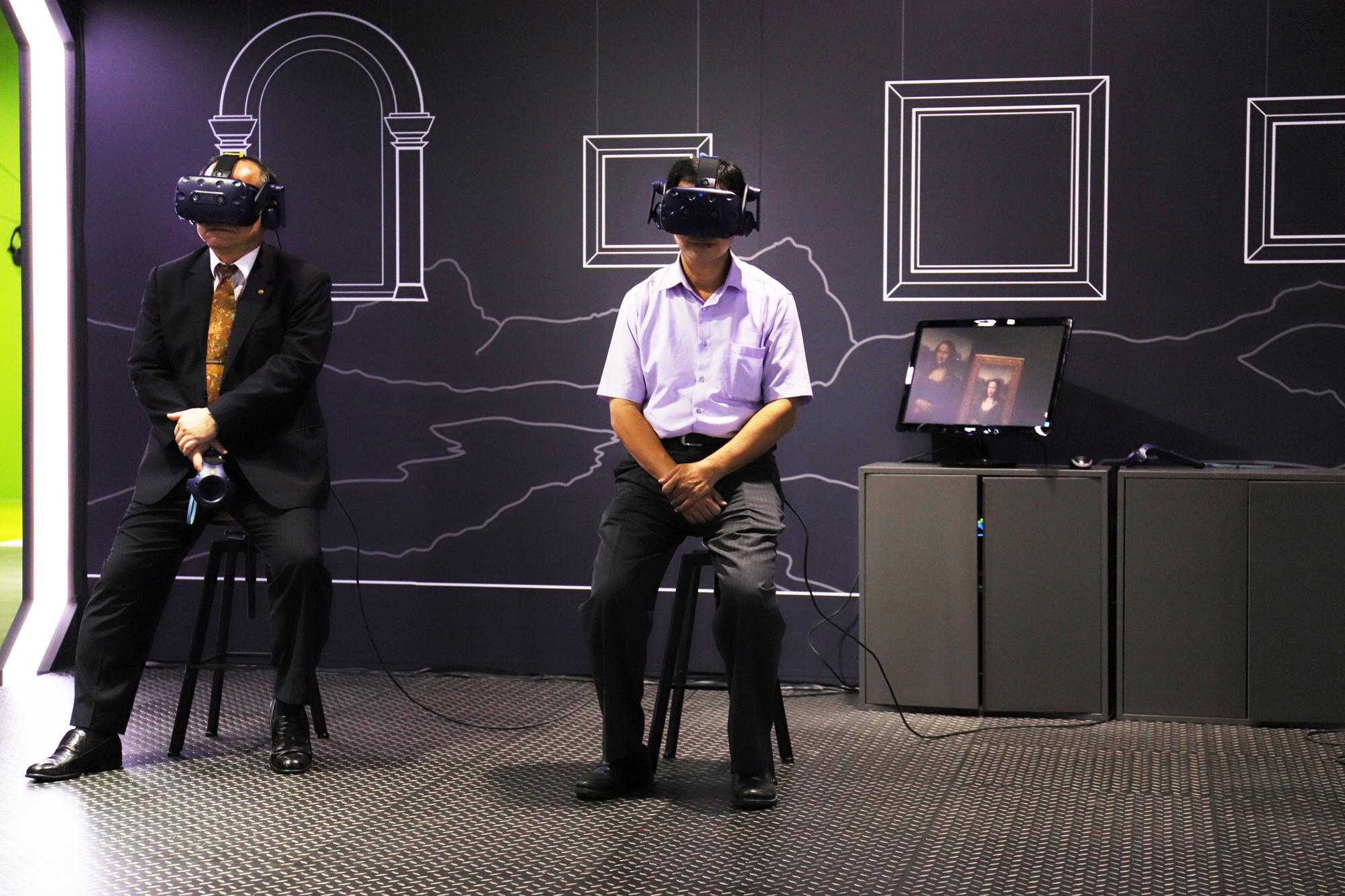 HTC新聞稿(左起高雄市政府秘書長陳鴻益、經濟部工業局顏鳳旗副組長體驗蒙娜麗莎越界視野VR體驗)