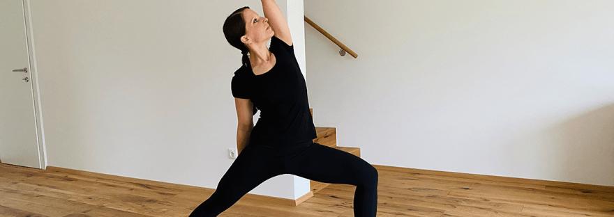 Frau zeigt eine Standhaltung (Kriegervariation) aus dem Yoga, die in den Sonnengruß integriert werden kann.
