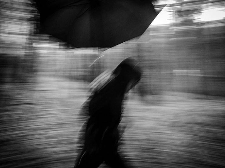 sw-Foto, jemand rennt mit Regenschirm vorbei