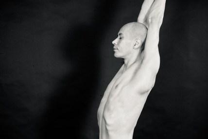 sw-Foto, Mann mit nacktem Oberkörper und Glatze streckt sich