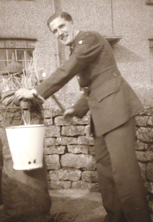 Sandy Munro using the pump outside Spinners Cottages