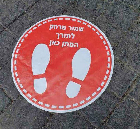 Adesivo rosso utilizzato nei mercati di tel aviv per garantire il distanziamento sociale