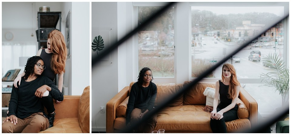 engaged-couple-lounging-on-leather-couch-in-front-of-large-window