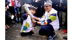 Achmad Dzulkarnain, pria difabel yang berkesempatan membaca obor Asian Games ketika tiba di Kabupaten Banyuwangi, Jawa Timur, Minggu (22/7/2018). (Foto: RRI)