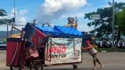 Satu pedagang mengevakuasi gerobaknya dagangannya akibat bentrok yang terjadi. (Foto: Riswan/SULTRAKINI.COM)