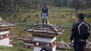 Indian tourist climbs sacred stupa.