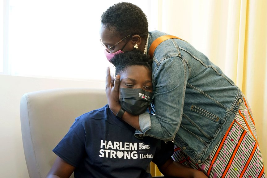 Julian Boyce, 14, gets a hug from his mother, Satrina Boyce, after he received his first Pfizer COVID-19 vaccination dose at NYC Health + Hospitals/Harlem, May 13th, 2021