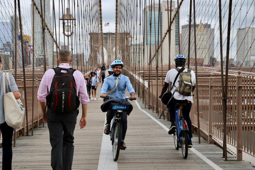 A person in a tie on a Citi Bike rides on the pedestrian path of the Brooklyn Bridge