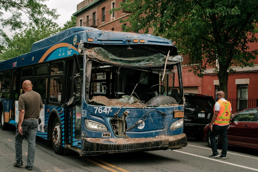 The damaged bus, with its front window shattered, and dust from the building is on the street
