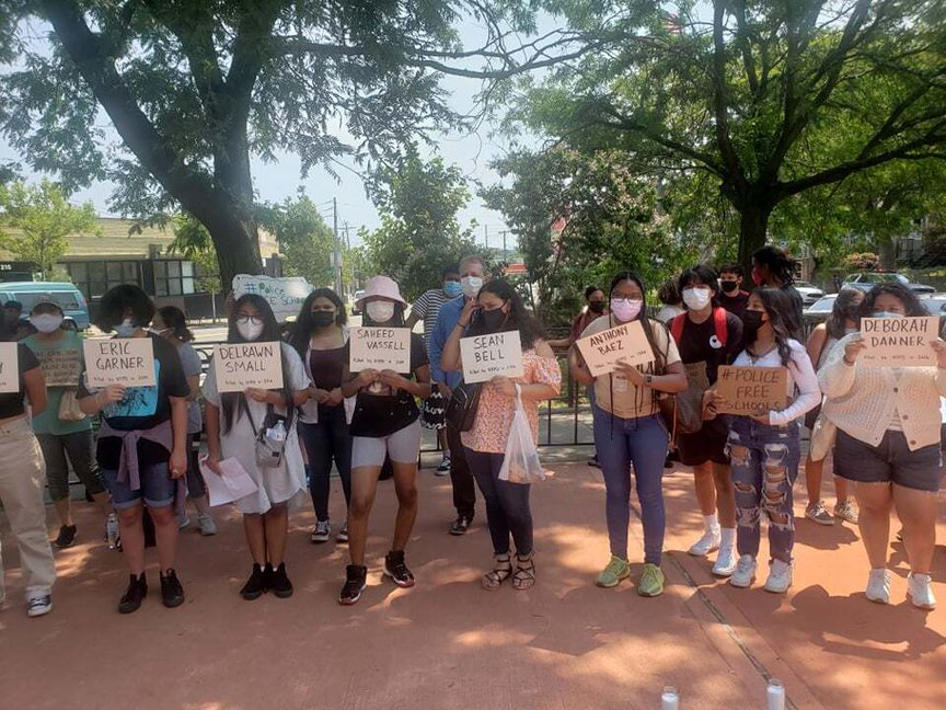 Young people hold up signs with the names of people killed by the NYPD at Tompkinsville Park.
