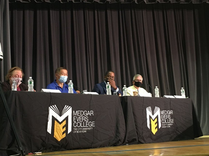 On a stage at Medgar Evers College, State Senators wear masks and listen to testimony