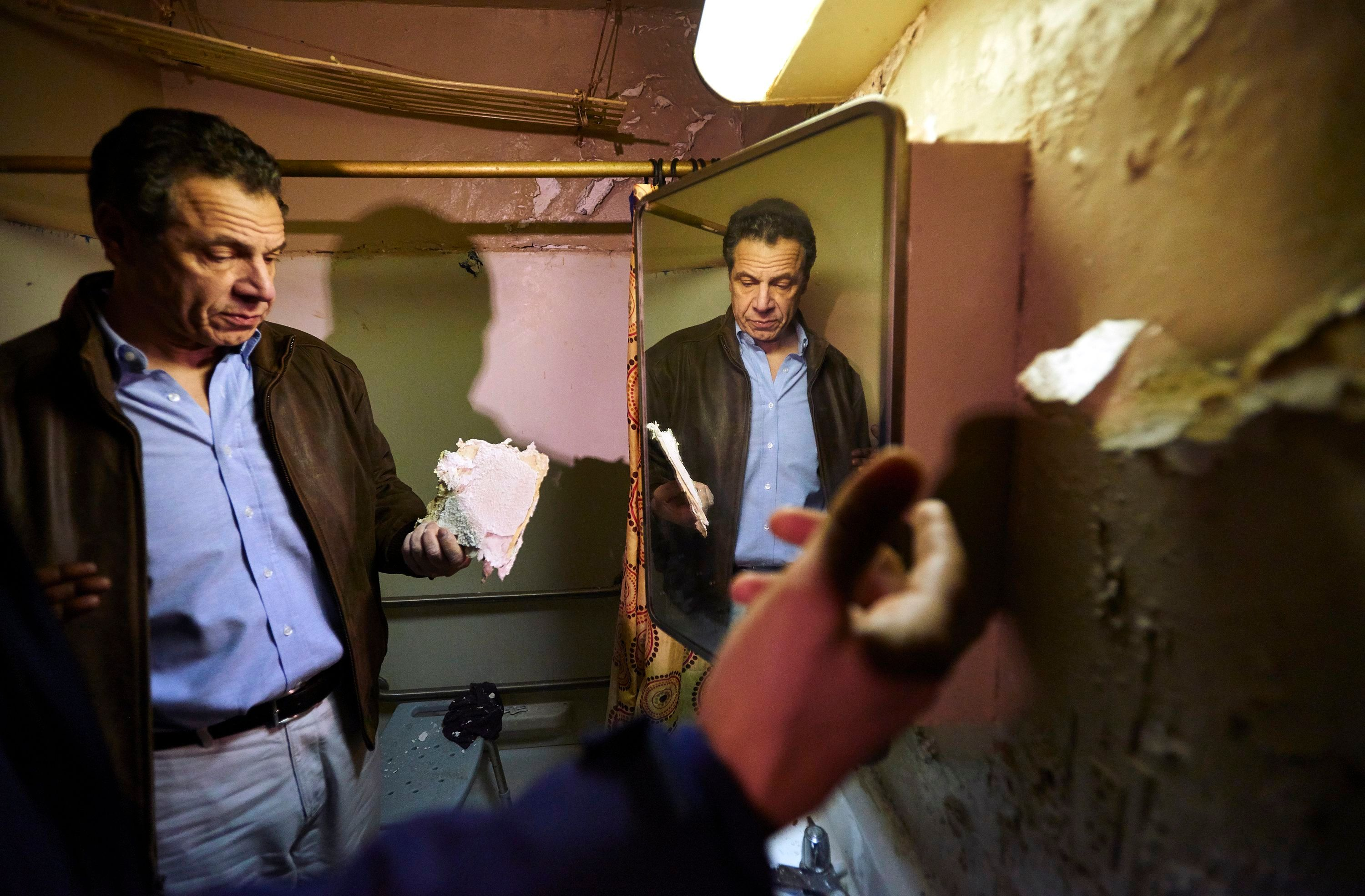 In 2018, Governor Andrew Cuomo examined a damaged piece of a bathroom wall during a tour of the Andrew Jackson Houses in the Bronx.