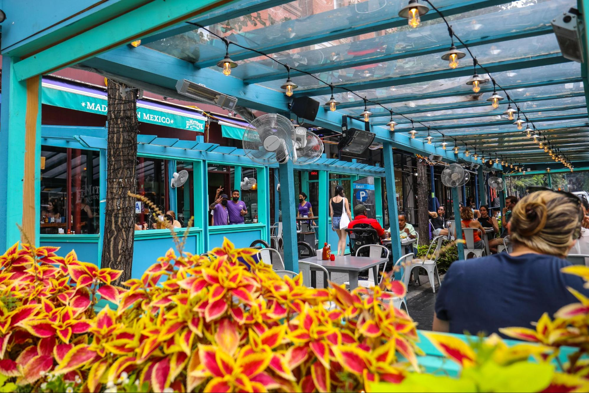 teal outdoor seating area with diners enjoying food
