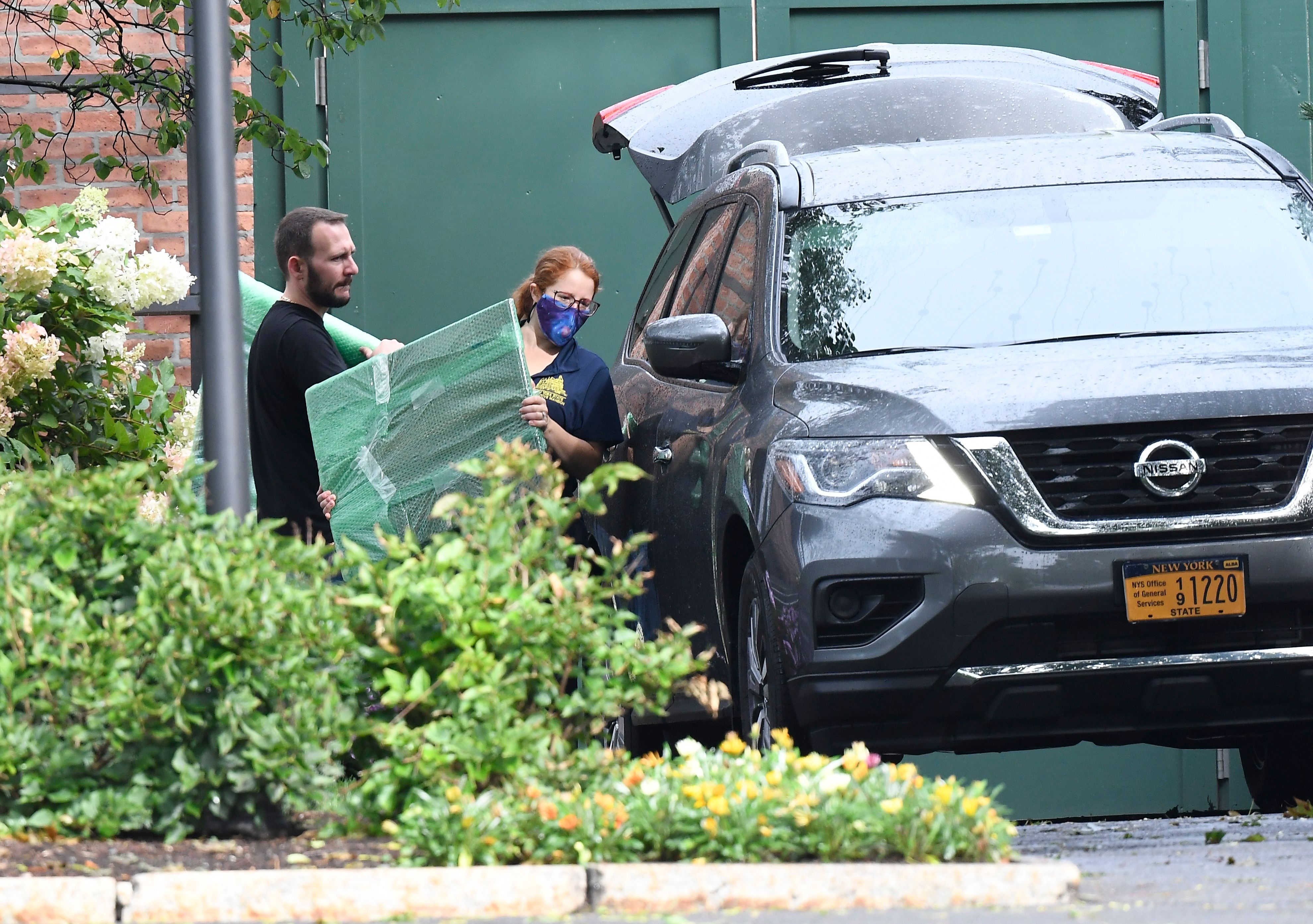 Employees from the state office of general services are seen moving items into an SUV outside the Governor's mansion