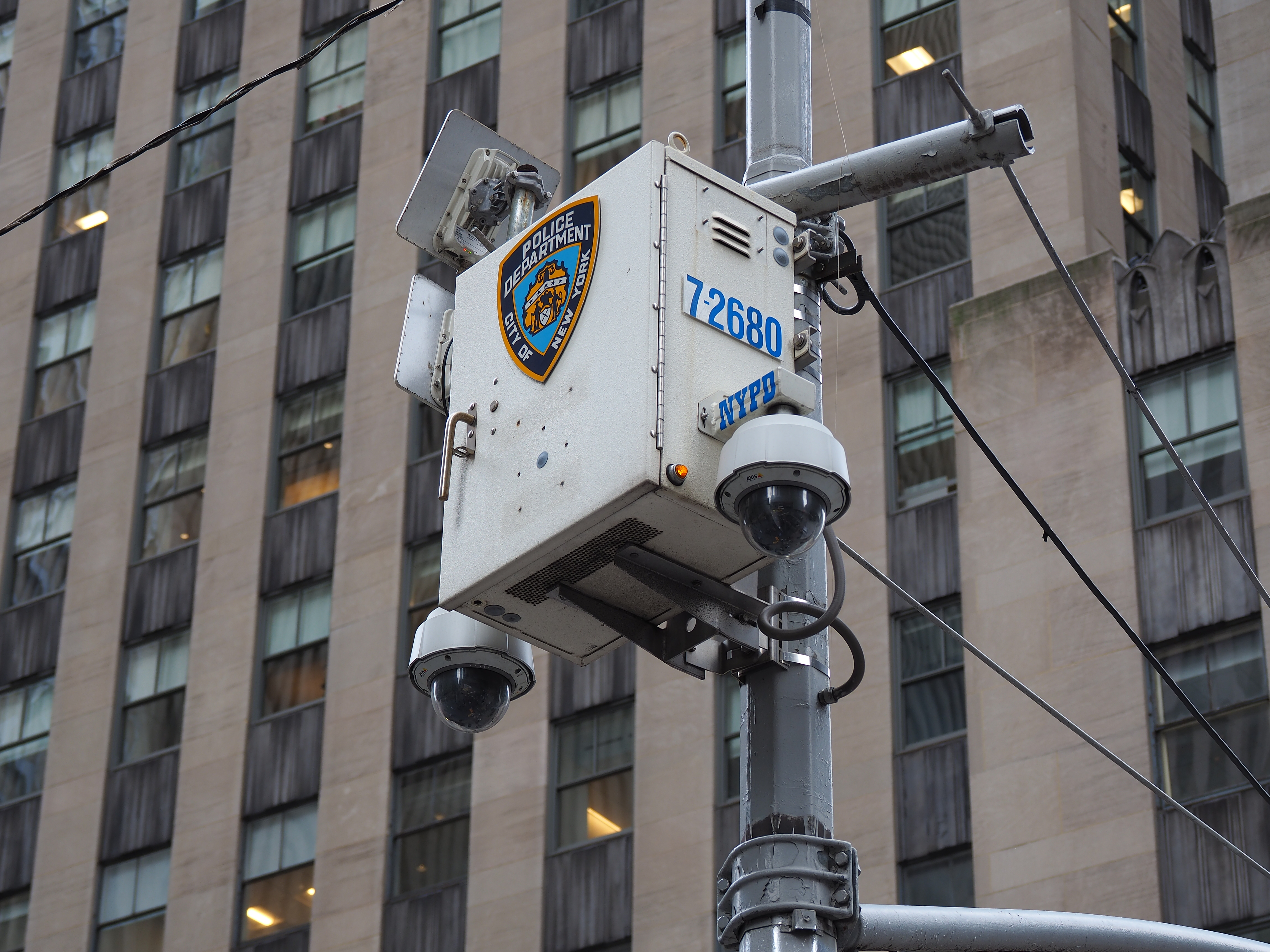 An NYPD surveillance camera - with multiple cameras and a white box that has an NYPD logo on it- on a pole near a tall office building