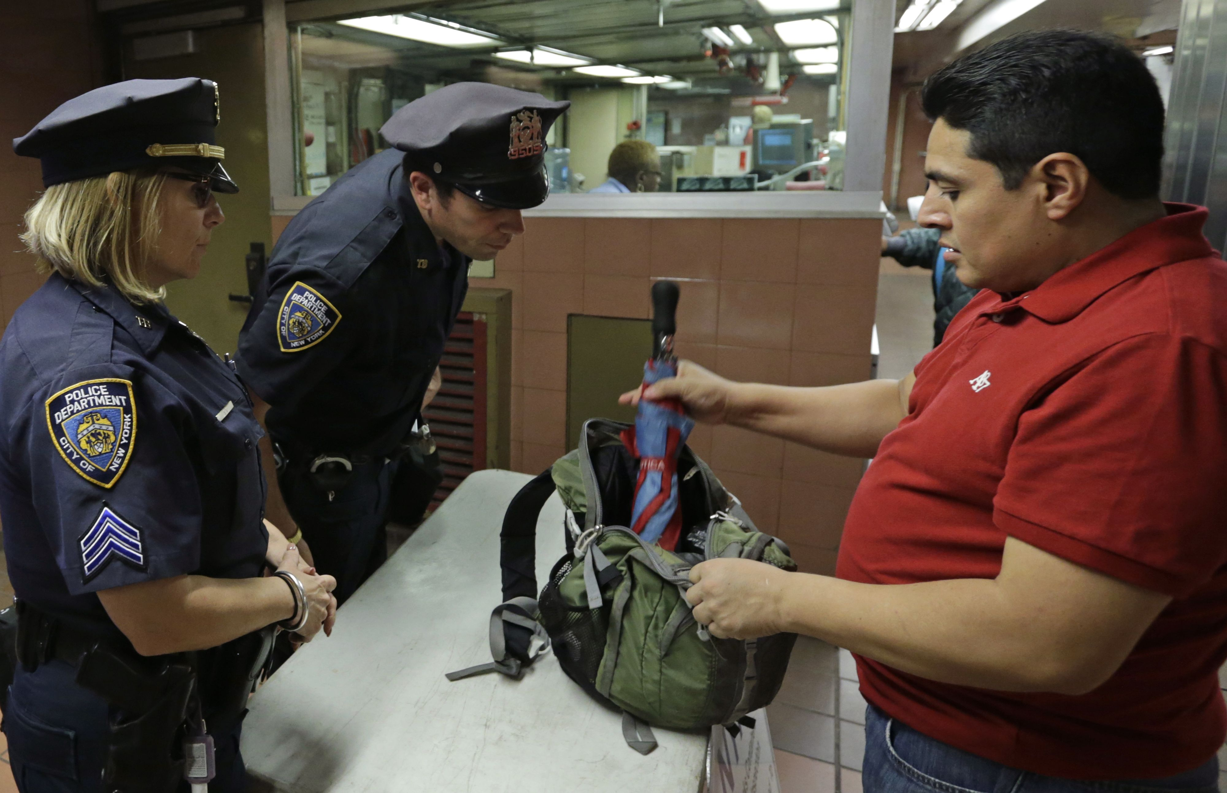 A commuter opens his brief case for police officers to examine its contents