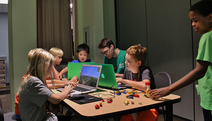 Multiple campers coding on computers