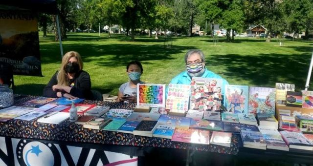 """One of several booths lining the walkways at North Park, this one sports pamphlets and merchandise representing smaller businesses in Billings, including one from """"Fursuit"""" the performing arts scene."""