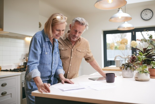 Mature Couple Reviewing Domestic Finances And Investments In Kitchen At Home Together