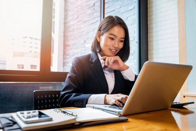 Closeup of businesswoman using laptop at office desk - searching web or browsing information.