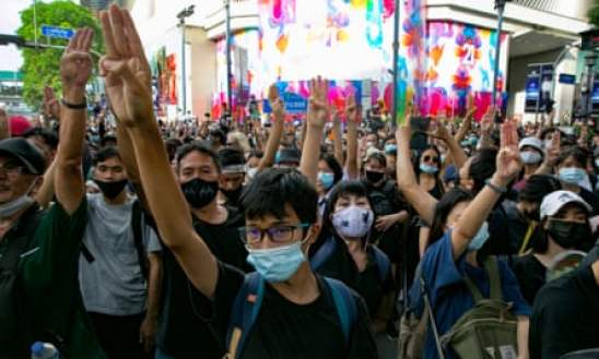 Thai students, all in masks, hold up a three finger salute (middle three fingers extended, thumb and pinkie touching over the palm) in protest of the Thai government.