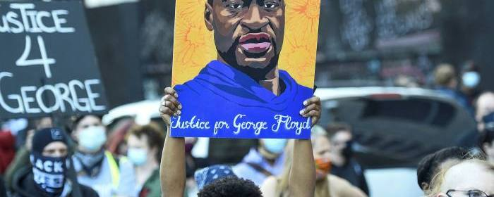 A protest in honor of George Floyd. A protester holds up a portrait of him.