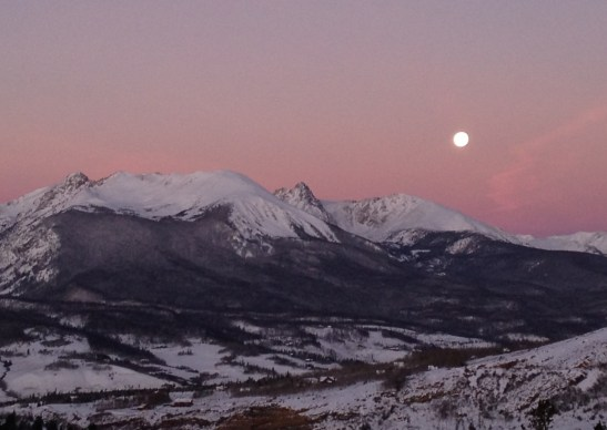 The moon sets over the Gore Range in the pink light of a Rocky Mountain dawn, the town of Silverthorne nestled in the valley below.