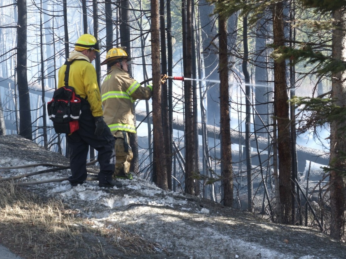 Firefighters standing in a snow berm extinguishing a small wildfire burning in March 2012 at 10,000 feet in the Colorado Rocky Mountains. This is not normal.