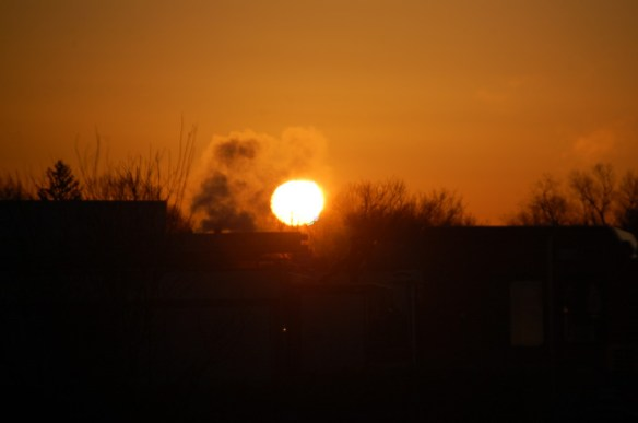 Steam rises in front of the sunrise on a cold winter morning