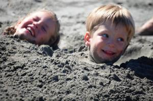 Olivia and Benson buried in sand at the beach in 2015