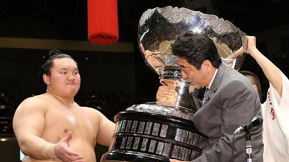 El Primer Ministro japonés Shinzo Abe entregando uno de los trofeos a Hakuho