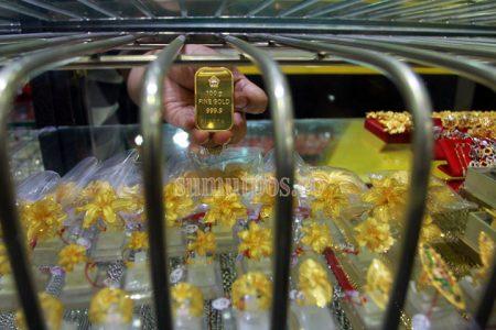TRIADI WIBOWO/SUMUT POS--Seorang pemilik usaha menunjukan batangan emas di salah satu toko emas di pasar Pringgan Medan, Jumat (14/14)