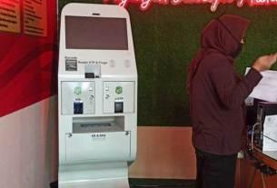 MESIN ADM: Seorang wanita beranjak pergi usai menggunakan mesin Anjungan Dukcapil Mandiri (ADM) di kantor Disdukcapil Kota Medan, Jalan Iskandar Medan, Selasa (10/11). Mesin ini sudah mulai dioperasikan sejak kemarin.