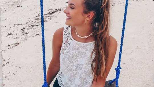 Веселая девчонка катается на качели на пляже