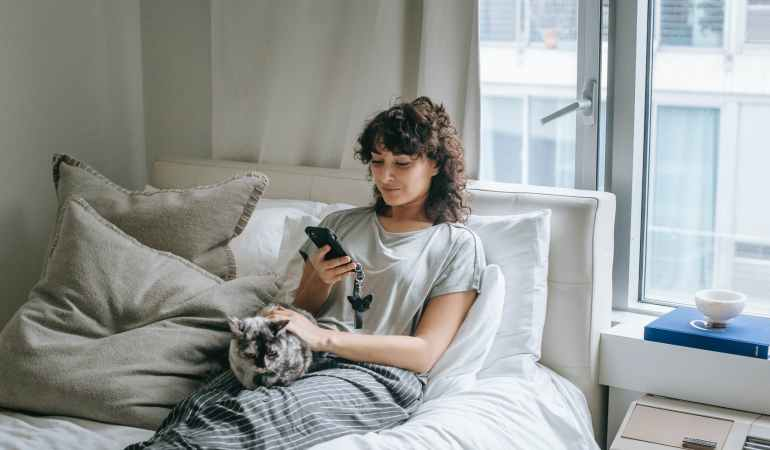 content woman browsing smartphone near cat