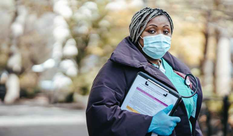 black female doctor in street with documents in epidemic