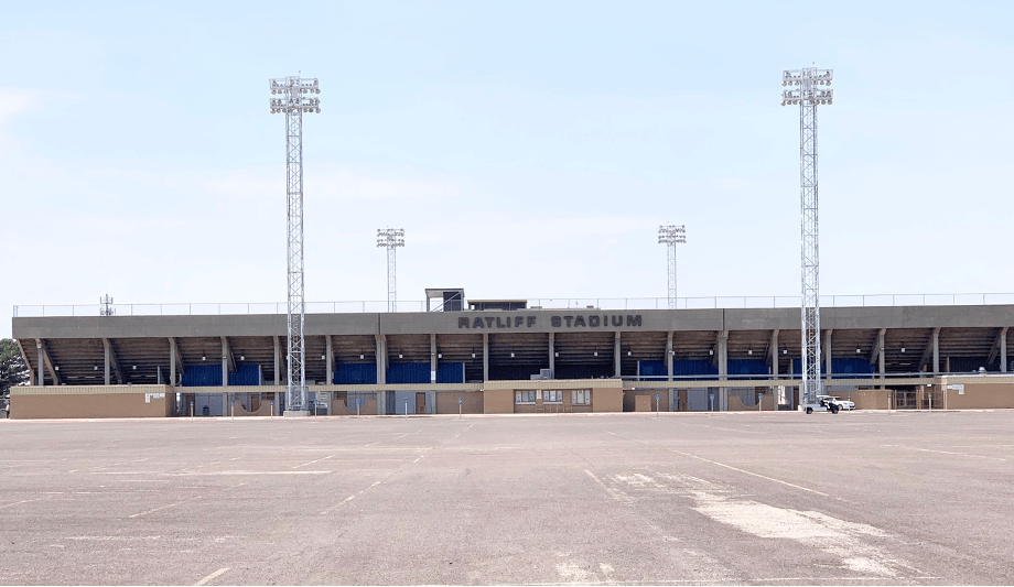 a head on photo of ratcliff stadium, with the name written atop the wide, flat entrance structure with an empty parking lot in front and two light structures, with two more beyond