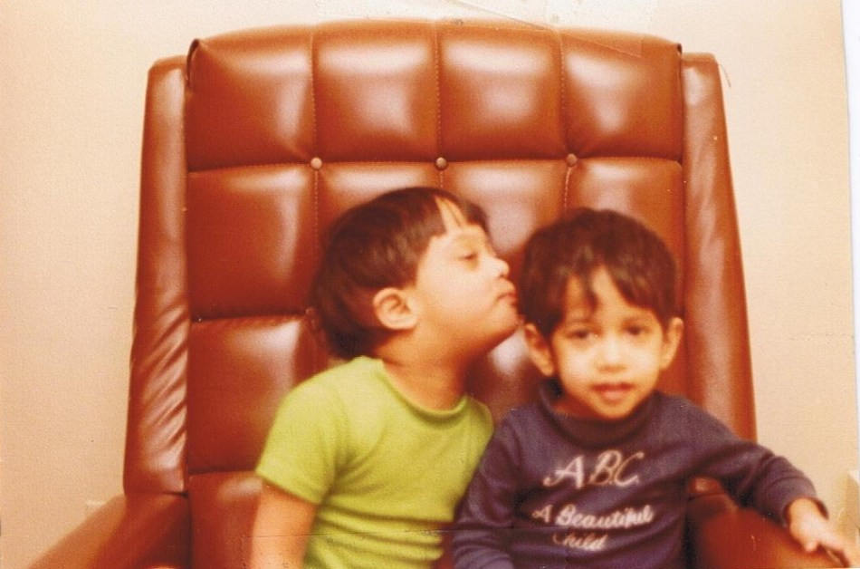 Das Vellody, left, as a young boy in a green shirt kissing the head of his brother Kishore, right, as a boy, in a blue shirt smiling at the camera; both sitting in a large brown office chair