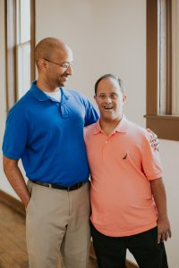 Kishore Vellody, left, in a blue polo and khaki pants and wearing glasses smiles down at his brother Das, right, in a pink polo smiling at the camera