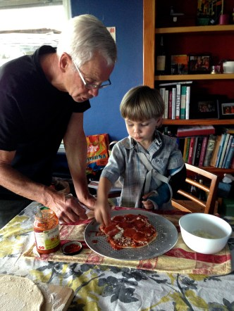Papa helping Ollie with his pizza