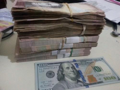 Sur cette photo Carlos illustre la dévaluation du Bolivar, la monnaie vénézuélienne. D'un côté, un billet de 100 $ et de l'autre, la même somme en Bolivar.