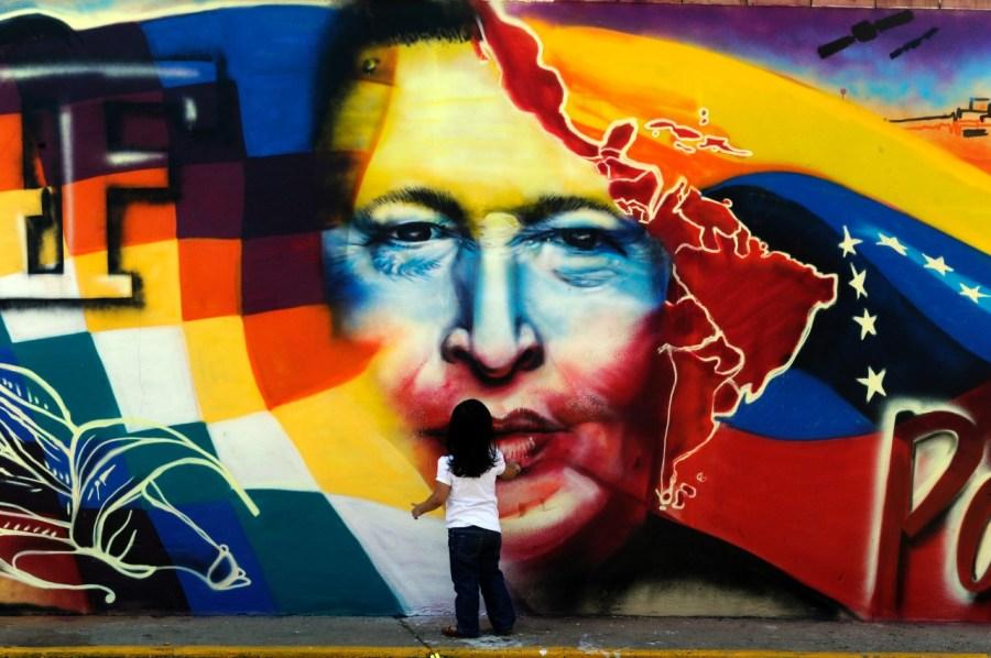 Une petite fille devant une fresque représentant Hugo Chavez - © JUAN BARRETO/AFP/Getty Images